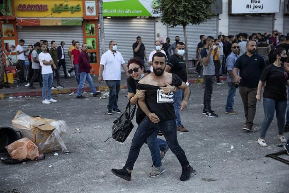 امرأة فلسطينية تحمي شاباً بعد اعتداء قوات الامن عليه في مدينة رام الله (شاهد)